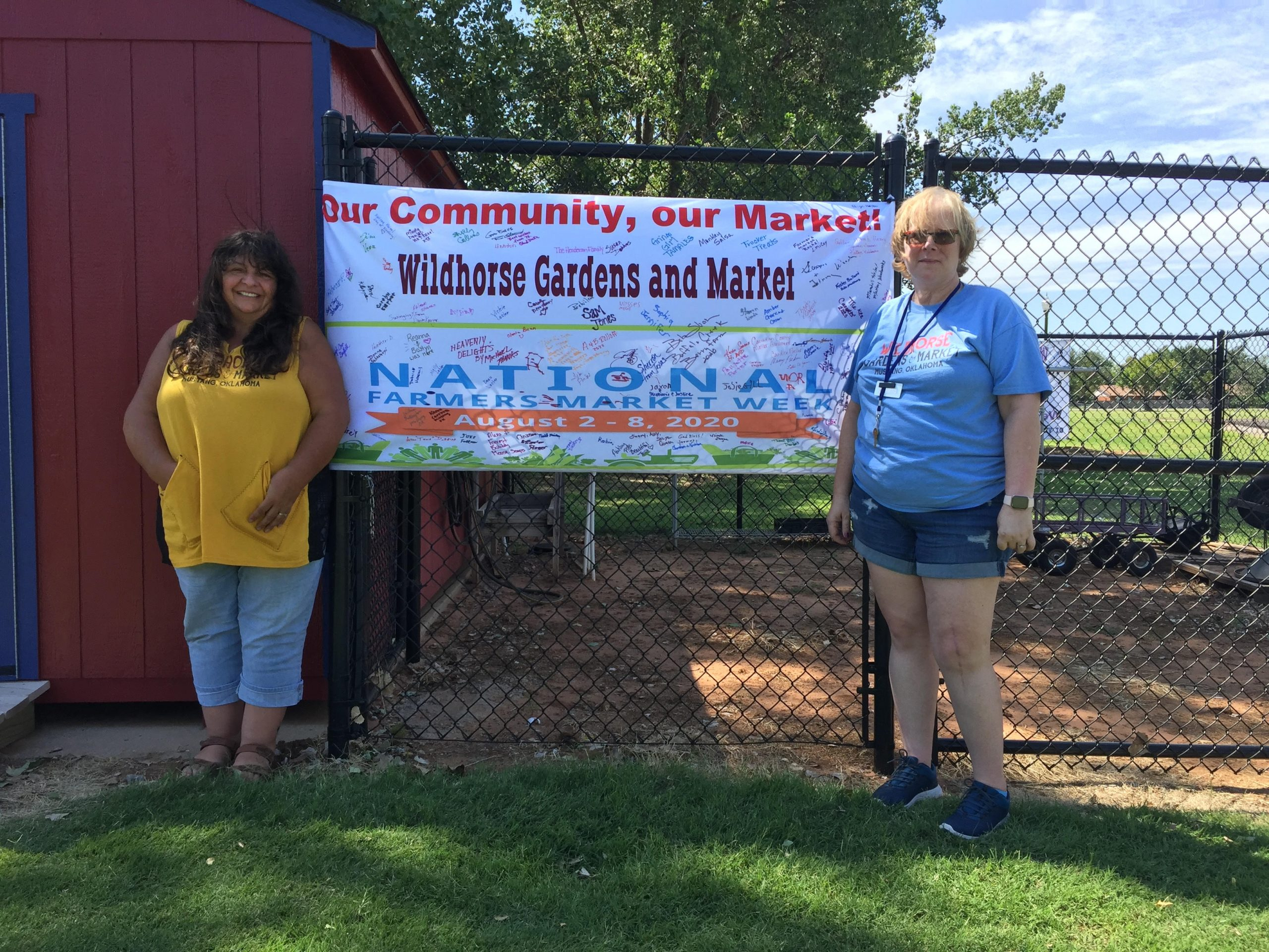 Volunteers Treasurer Betty Schwartz and Market Manager Shelly Collins pose with their banner at Wildhorse Market, Mustang, Oklahoma.
