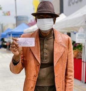 Black man in a fedora, orange jacket and medical mask holds up a voucher for the senior farmers market nutrition program.